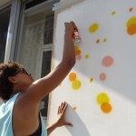 nancy is holding an aerosol can spraying yellow and orange dots on a white background