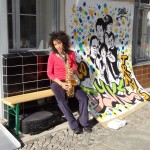 layla sitting on a bench outside the gallery with a sax in their hand, nxt to grafitti by nancy rhode